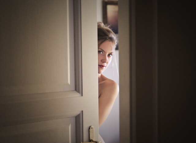 žena vykukující za dveřmi