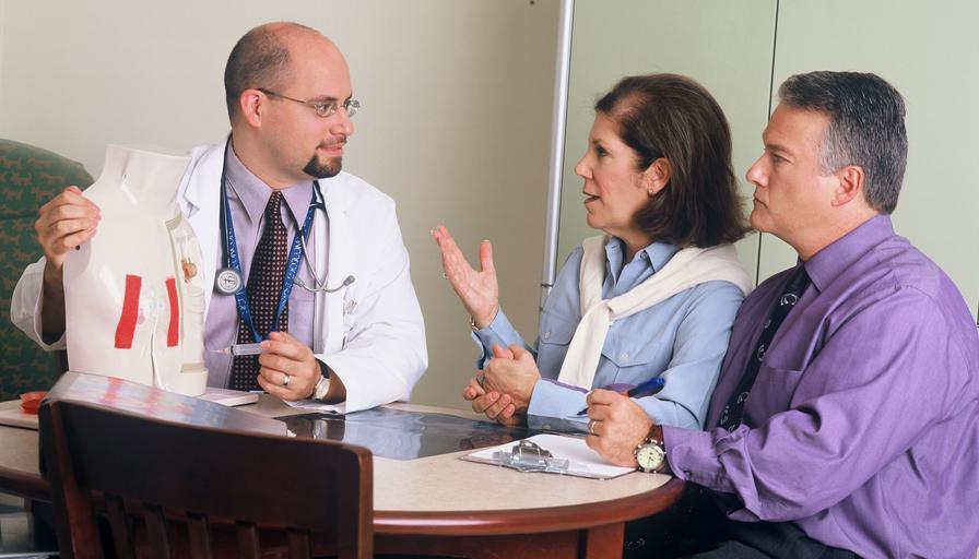 doktor a dva pacienti, muž a žena, sedí za stolem a povídají si