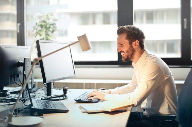 smějící se muž u počítače