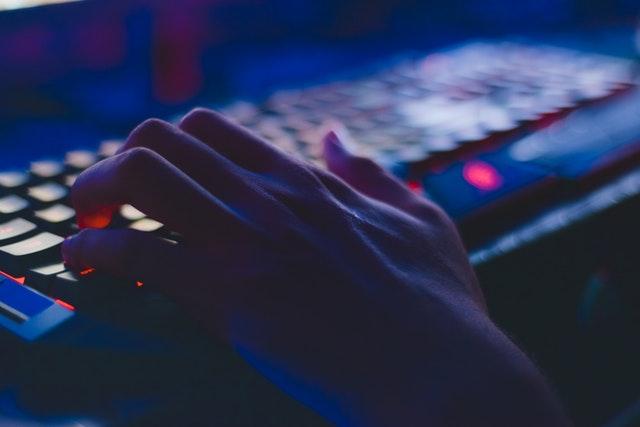 ruka na klávesnici ve tmě, detail