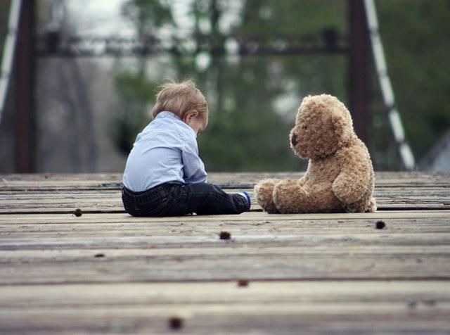 chlapec s plyšovým medvědem na dřevěném mostku