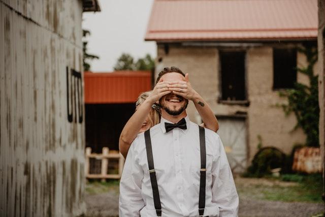 Žena stojící za mužem a držící mu rukama zakryté oči